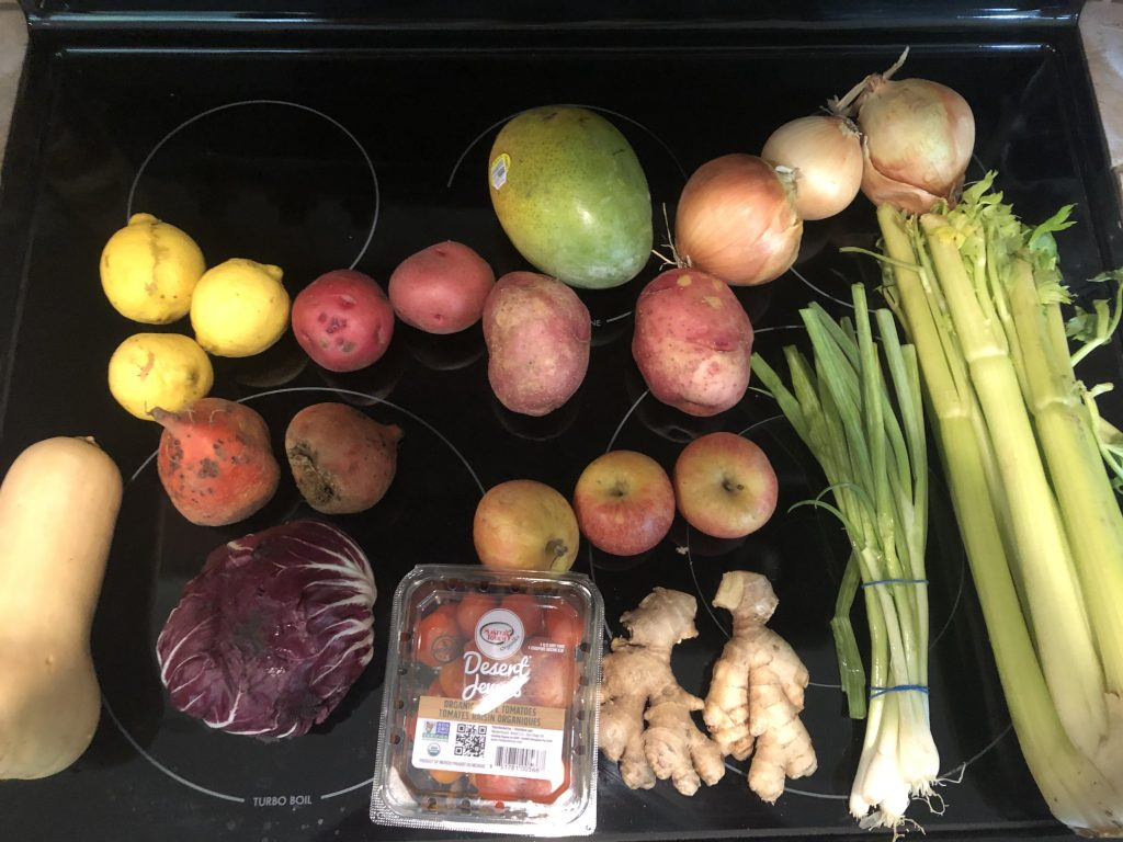A picture of various fruits and vegetables on a stove range